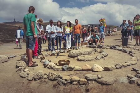 Bucegi Mountains, Romania - August 6, 2016: People attend a spiritual ritual organized around a spiral of stones near the Sphinx, the sacred megalith located at 2,216 m altitude in Bucegi Mountains. Editorial