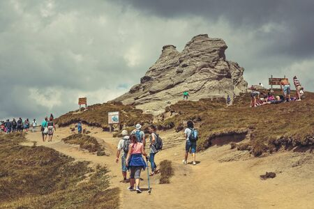 megalith: Bucegi Mountains, Romania - August 6, 2016: Hundreds of people hike the trails to the Sphinx, the mythical megalith with human face resemblance located at 2,216 m altitude in Bucegi Mountains.