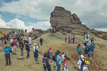 megalith: Bucegi Mountains, Romania - August 6, 2016: Tourists enjoy the performance of four Romanian women in colorful traditional costumes playing the tulnic near the Sphinx megalith in Bucegi mountains.