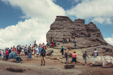megalith: Bucegi Mountains, Romania - August 6, 2016: Tourists come to contemplate, meditate or rest at Sphinx, the legendary megalith with human face likeness located at 2,216 m altitude in Bucegi Mountains.