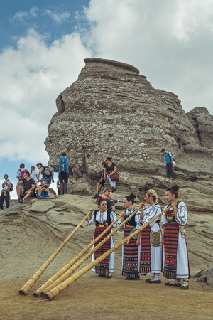 blowers: Bucegi Mountains, Romania - August 6, 2016: Group of young Romanian female artists wearing colorful traditional costumes play the tulnic near the legendary Sphinx megalith in Bucegi mountains.
