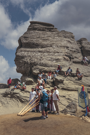megalith: Bucegi Mountains, Romania - August 6, 2016: People come to contemplate, meditate or rest at Sphinx, the famous sacred megalith with human face likeness located at 2,216 m altitude in Bucegi Mountains.