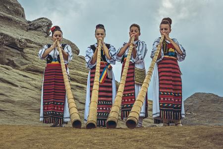 ブチェジ山脈、ルーマニア - 2016 年 8 月 6 日: ルーマニア女性 tulnic 選手のグループ伝説のスフィンクス メガリス ブチェジ山脈高原にカラフルな伝統