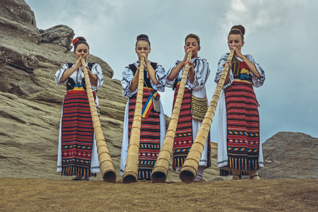 ethnology: Bucegi Mountains, Romania - August 6, 2016: Group of Romanian female tulnic players dressed in colorful traditional costumes on Bucegi mountains plateau near the legendary Sphinx megalith.