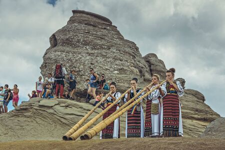 megalith: Bucegi Mountains, Romania - August 6, 2016: Young Romanian women dressed in colorful traditional costumes play the tulnic near the Sphinx megalith in Bucegi mountains.