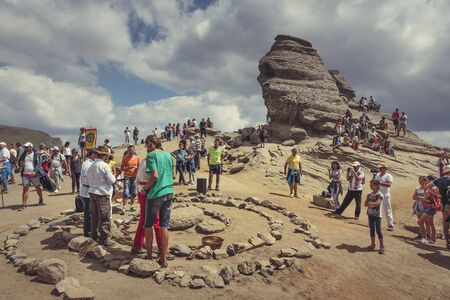 megalith: Bucegi Mountains, Romania - August 6, 2016: Tourists participate to a spiritual ritual organized around a spiral of stones near the Sphinx, the sacred megalith located on the Bucegi Mountains plateau. Editorial