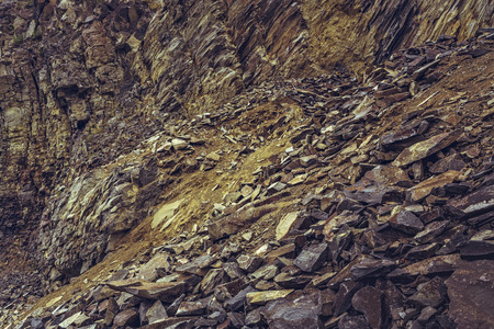 strata: Arid strata volcanic stone cliff and rock debris in an old deserted basalt quarry near the Racos extinct volcano in Brasov county, Romania. Stock Photo