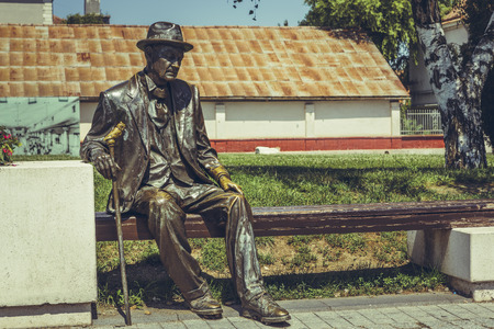 fellow: Alba Iulia, Romania - July 24, 2016: Bronze statue depicting a sad and tired old fellow citizen resting on a bench in Alba Carolina Citadel square.
