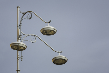 Closeup of retro stylish street lamppost with three bulbs over grey cloudy sky. Copy space. Stock Photo