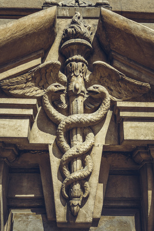 twined: Bucharest, Romania - April 22, 2014: Carved bas-relief depicting two serpents twined around the winged caduceus staff as a symbol of commerce, on the frontispiece of the Stock Exchange Palace. Editorial