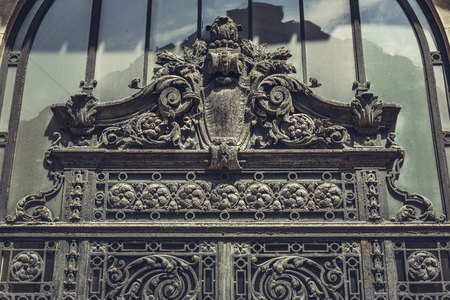 sumptuous: Bucharest, Romania - April 22, 2014: Architectural detail of the weathered sumptuous iron door at the entrance of Stock Exchange Palace facade decorated in classic French style.