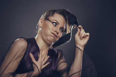 sicken: Fancy woman in satin lingerie sicken by her black high heel shoe stinky odor. Footwear bad hygiene. Smelly shoe.