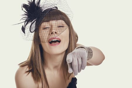 Portrait of an amused beautiful young woman wearing a black vintage style light feather hat, net veil and gloves while pointing finger and laughing at you against bright background. Stock Photo