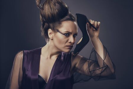 Fancy woman in sexy low-cut satin lingerie smelling a stinky black high heel shoe over dark background. Stylish woman making disgust face expression when smelling unpleasant odor of her shoe.