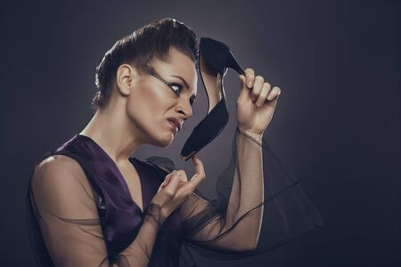 sicken: Side portrait of a fancy extravagant woman in sexy satin lingerie displeased by her black high heel shoe smell against dark background.