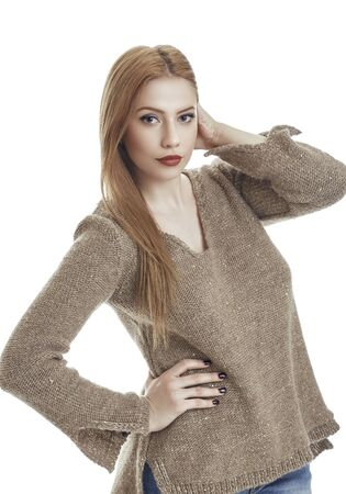 Attractive sensual young woman wearing warm homemade knitted pullover. Gorgeous flirtatious female fashion model in winter woolen sweater posing with hand on hip against white background.