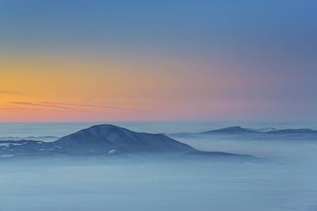 Majestic winter view with sunset over the misty valleys of the Carpathians mountains, Transylvania region, Romania.
