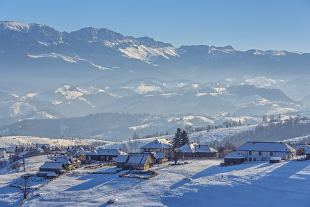 Picturesque rural landscape with traditional Romanian hamlet in the valley of Bucegi mountains on a cold winter afternoon, Pestera village, Bran-Rucar pass, Transylvania region, Romania. Stockfoto