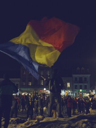 ordenanza: Brasov, Romania - February 4, 2017: Protester waves giant Romanian national flag during peaceful mass rally in the Council Square against controversial emergency ordinance on amnesty and pardon law. Editorial