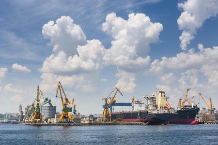 Toneel mening met cumuluswolken boven industriële zeehaven met grote vrachtschepen die voor het verschepen in Constanta, Roemenië worden gedokt.