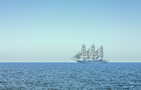 Three masted tall ship in full sails on the Black Sea on the horizon.
