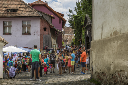 Sighisoara, Romania - July 26, 2014: Tourists stroll the old cobblestone streets in the medieval citadel of Sighisoara, one of the few still inhabited citadels in Europe Editorial