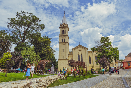 church steeple: Sighisoara, Romania - July 26, 2014: Tourists come to visit the Saint Joseph Roman-Catholic Cathedral, one of the famous oldest churches in the medieval citadel of Sighisoara.
