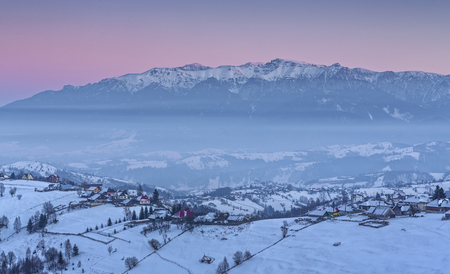 Countryside landscape with Romanian village in the valleys of the Bucegi mountains on a cold winter evening in Pestera, Brasov county, Transylvania region, Romania.