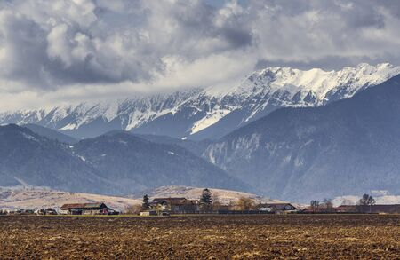 Rural landscape with plowed fields and snow-capped Piatra Craiului mountain range during springtime in Brasov county, Romania.