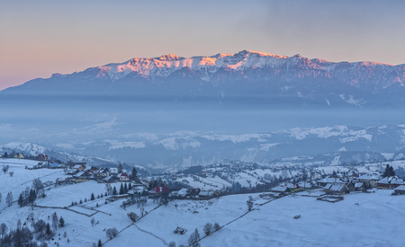 Magnificent rural view with the snowy Rucar-Bran pass in the valley of Bucegi mountains at sunset, Pestera village, Brasov county, Transylvania region, Romania. Stock Photo