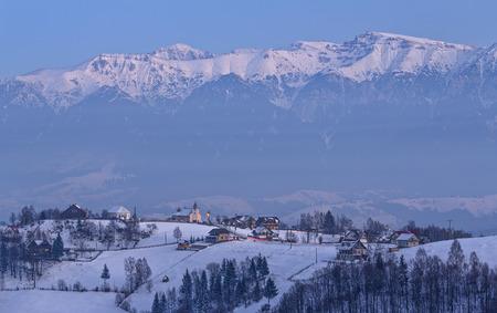 Evening fall over snowy Pestera village in the frozen valleys of Bucegi mountains, Rucar-Bran pass, Transylvania region, Romania.