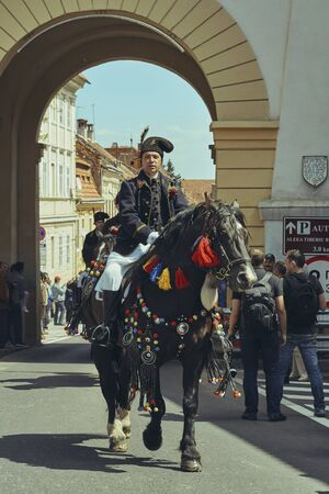 Brasov, Romania - April 27, 2014: Horseman rides thoroughbred stallion adorned with traditional decorations during the Youths of Brasov (Junii Brasovului) Parade. Editorial