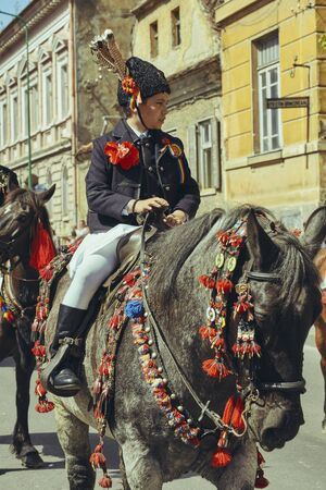 Brasov, Romania - April 27, 2014: Young boy in traditional costume rides adorned stallion during the Junii Brasovului (Youths of Brasov) festival. Editorial