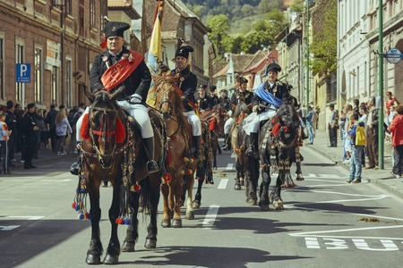 Brasov, Romania - April 27, 2014: Horsemen ride thoroughbred stallions adorned with traditional decorations during the Traditional Parade of the Youths of Brasov. Editorial