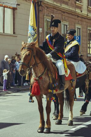Brasov, Romania - April 27, 2014: Horseman rides chestnut horse adorned with traditional decorations and holds a flag during the Youths of Brasov (Junii Brasovului) Parade. Editorial