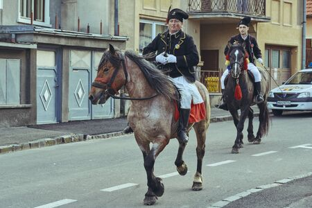 Brasov, Romania - April 27, 2014: Horsemen ride thoroughbred stallions adorned with traditional decorations during the Youths of Brasov (Junii Brasovului) Parade.