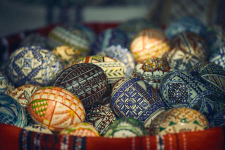Pile of colorful manually crafted, painted decorative Easter eggs in a basket. Closeup, shallow depth of field, selective focus.