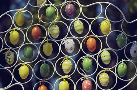 Colorful painted decorative Easter eggs hanging by an iron frame outside. Closeup, shallow depth of field.