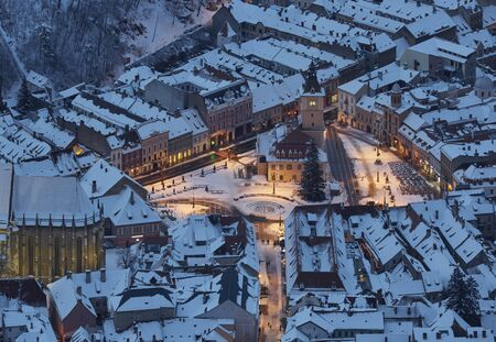 Aerial twilight cityscape of the snowy Council Square in the historic center of Brasov city, Romania. Stock Photo