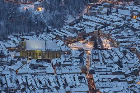 Aerial twilight view of the snowy Council Square in the historic center of Brasov city, Romania. Stock Photo