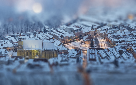 Aerial twilight cityscape of the snowy Council Square in the historic center of Brasov city, Romania. Tilt-shift blur effect.