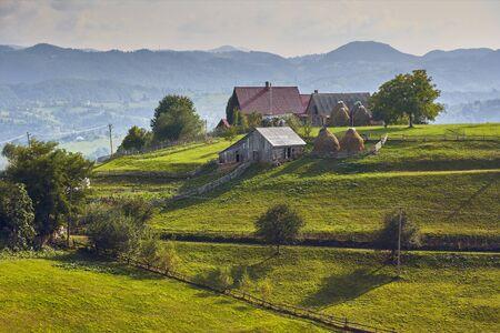 Springtime rural landscape. Traditional Transylvanian village on top of a green hill in Brasov county, Transylvania, Romania.