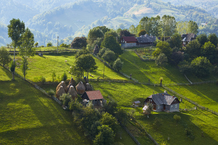 Springtime rural scenery in a traditional Transylvanian hamlet on top of a green hill in Magura village, Brasov county, Romania. Stock Photo