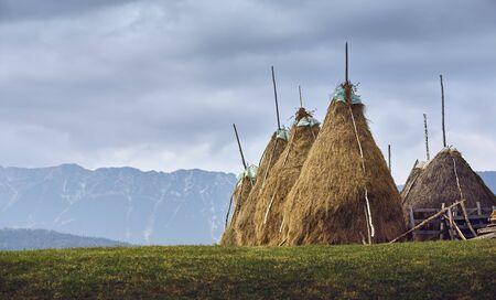 Rural cloudy landscape with haystacks near Piatra Craiului mountains in Transylvania region, Romania.