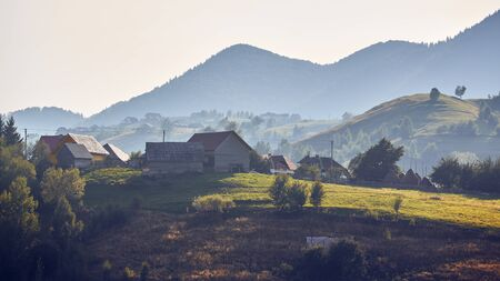 Rural landscape. Early morning sunlight over the hills and vales in Bran-Rucar pass, Pestera village, Brasov county, Transylvania, Romania.