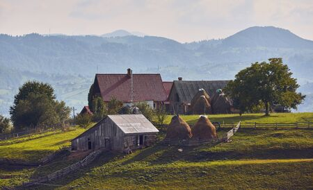 Springtime rural landscape. Traditional Transylvanian house with rustic wooden barn, cowshed, hayricks and green pasture in Brasov county, Transylvania, Romania.