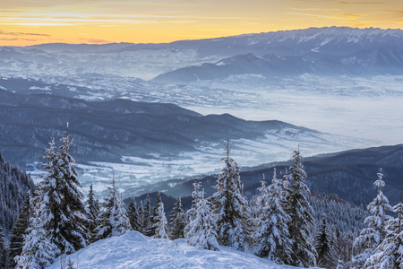 Winter landscape with golden sunset over Carpathians mountains, Romania. Snowy misty valleys at the base of Postavaru and Piatra Craiului mountains, Brasov county, Transylvania region.