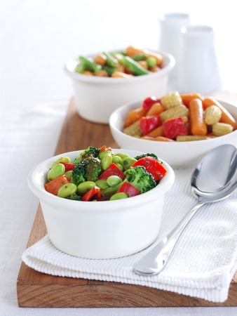 Bean Salads in white china bowls on a wooden board