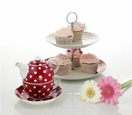 high tea: Cup cakes and tea pot on isolated white background Stock Photo