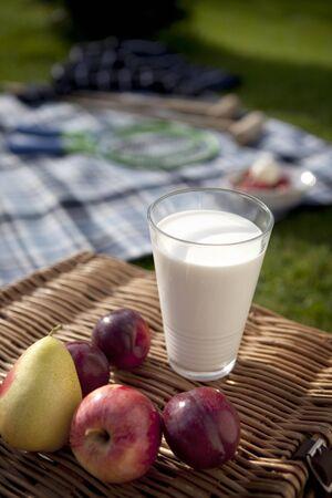 Glass of fresh milk sat on a picnic hamper